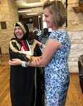 Paula Johnson welcomes Aliyah Khalaf Saleh, known as Umm Qusay in Iraq, to the Warrior and Family Support Center as part of the Iraqi humanitarian's visit to Joint Base San Antonio-Fort Sam Houston.