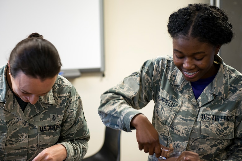 Master Sgt. Amanda Lewis, left, 23d Aerospace Medicine Squadron (AMDS) public health flight chief, and Airman 1st Class Angel Brumfield, 23d AMDS public health technician, open their meals, ready to eat (MREs) during an MRE open-package inspection, April 6, 2018, at Moody Air Force Base, Ga. Airmen from Public Health examine the MREs for defects and overall quality and determine whether they'll be utilized here, at other bases or to condemn the batch. Public Health monitors more than 8,400 MREs yearly to ensure they are safe and fit for consumption, so as to maintain a healthy fighting force. (U.S. Air Force photo by Airman 1st Class Erick Requadt)