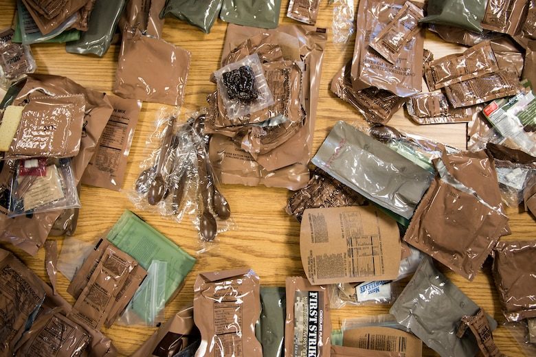 Meals, ready to eat (MREs) rest on a table during an MRE open-package inspection, April 6, 2018, at Moody Air Force Base, Ga. Airmen from Public Health examine the MREs for defects and overall quality and determine whether they'll be utilized here, at other bases or to condemn the batch. Public Health monitors more than 8,400 MREs yearly to ensure they are safe and fit for consumption, so as to maintain a healthy fighting force. (U.S. Air Force photo by Airman 1st Class Erick Requadt)