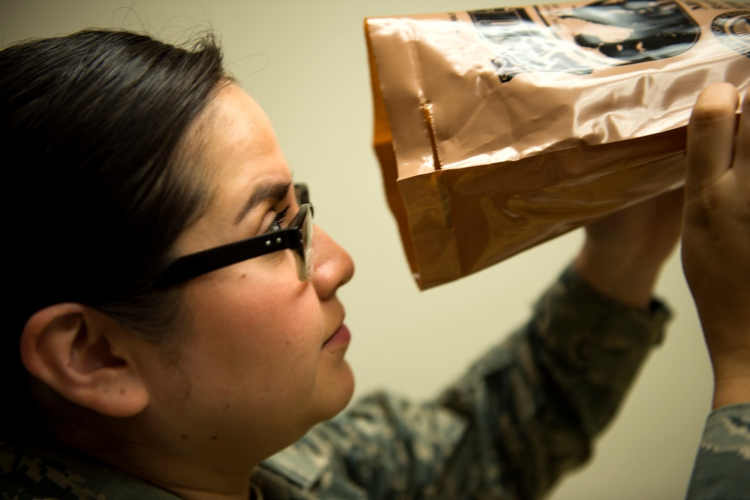 Senior Airman Evelyn Alvarado, 23d Aerospace Medicine Squadron meal, ready to eat (MRE) program manager, examines the inside of an MRE for holes during an MRE open-package inspection, April 6, 2018, at Moody Air Force Base, Ga. Airmen from Public Health examine the MREs for defects and overall quality and determine whether they'll be utilized here, at other bases or to condemn the batch. Public Health monitors more than 8,400 MREs yearly to ensure they are safe and fit for consumption, so as to maintain a healthy fighting force. (U.S. Air Force photo by Airman 1st Class Erick Requadt)