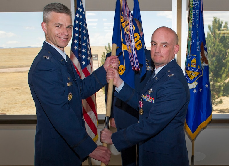 Col. Mark Stafford passes the 7th Space Operations Squadron guidon to Col. Stephen Slade, 310th Operations Group commander, as he relinquishes command during the change of command ceremony on Sunday, Apr. 8th, 2018.