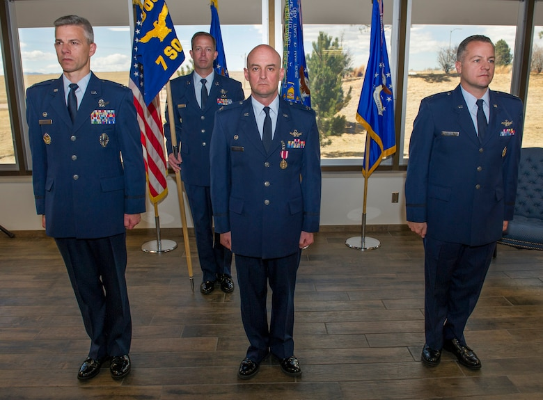 Col. Stephen Slade, 310th Operations Group commander, Col. Mark Stafford, outgoing 7th Space Operations Squadron commander, and Lieutenant Col. James Hogan, incoming 7 SOPS commander, stand at attention during the change of command ceremony on Sunday, Apr. 8th, 2018.