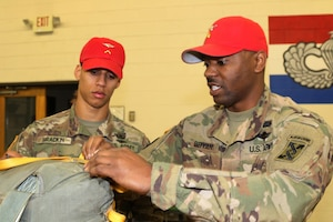 Army Sgt. Sean M. Bryant of Macon, Ga., shows Army Pvt. Joshua I. Brackin of Dothan, Ala., where the parachute static lines need to be checked for defects at Fort Valley, Ga.