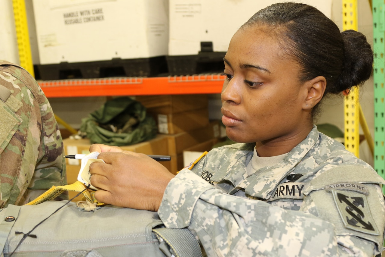 Army Spc. Arnesha S. Noble from Warner Robins, Ga., a parachute rigger with the 421st Quartermaster Company, signs her name after inspecting a parachute.