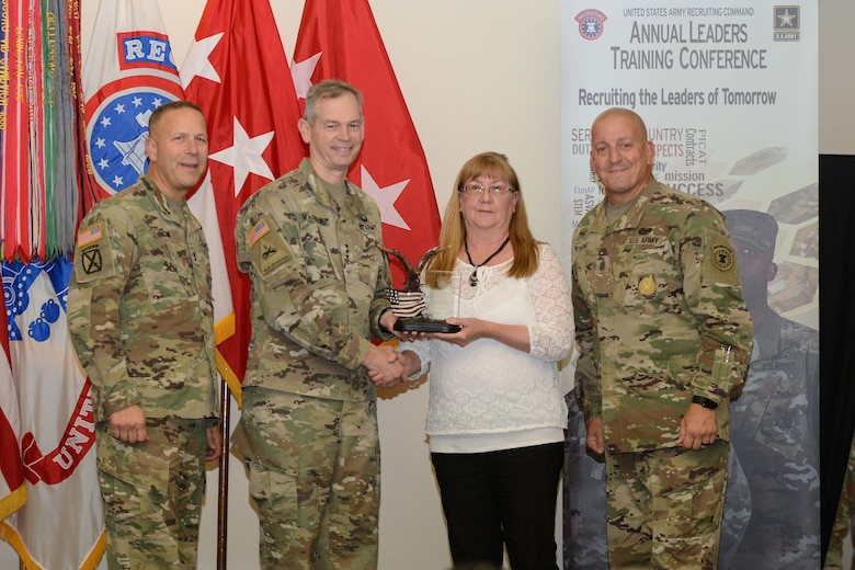 Three Soldiers present award to one civilian