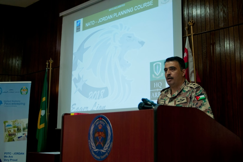 Jordan Armed Forces Lt. Col. Mahkmoud Bani-Issa, Military Training Directorate joint exercises senior staff, addresses NATO, Jordanian, and American officers prior to the capstone event of a NATO planning course near Amman, Jordan, April 4, 2018. Students in the course presented two potential courses of action in response to a simulated invasion and received feedback from senior officers.