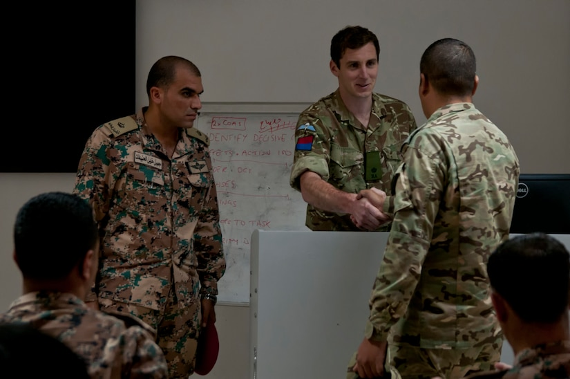 British Army Maj. James Beechey, a planner with the joint fires and information branch of the NATO Allied Rapid Reaction Corps, presents graduation certificates to Jordanian and American officers after completion of a NATO planning course near Amman, Jordan, April 4, 2018.