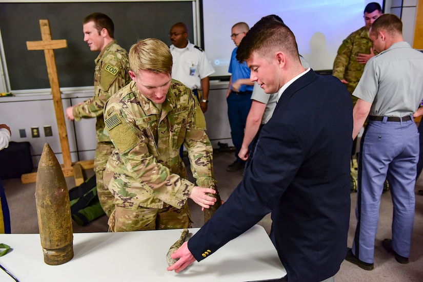 Senior Airman Jonathan Alvin, left, 628th Civil Engineer Squadron explosive ordnance disposal technician, describes different types of military ordnance to Cadet Kelbey Oakes, at The Citadel, April 3, 2018.