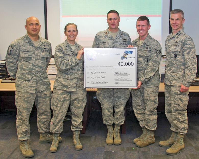 "Col. Traci Kueker-Murphy, 310th Space Wing commander, and Col. Stephen Slade, 310th Operations Group commander, present members of the 6th Space Operations Squadron with a celebratory ""check"" to mark their completion of the squadron's 40,000th satellite contact on Tuesday, Mar. 20, 2018."