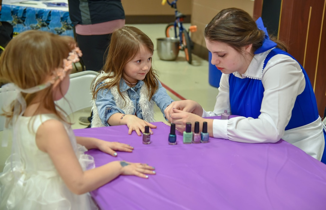 Addison and Baylee Johnson, daughters of 114th Fighter Wing members Master Sgt. Brian Johnson and Senior Master Sgt. Beth Johnson, gets their nails painted by Sophia Gapp, South Dakota National Guard Youth Council member, during the Princess and Super Hero Day Camp April 7, 2018, at the National Guard Armory, Sioux Falls, S.D.