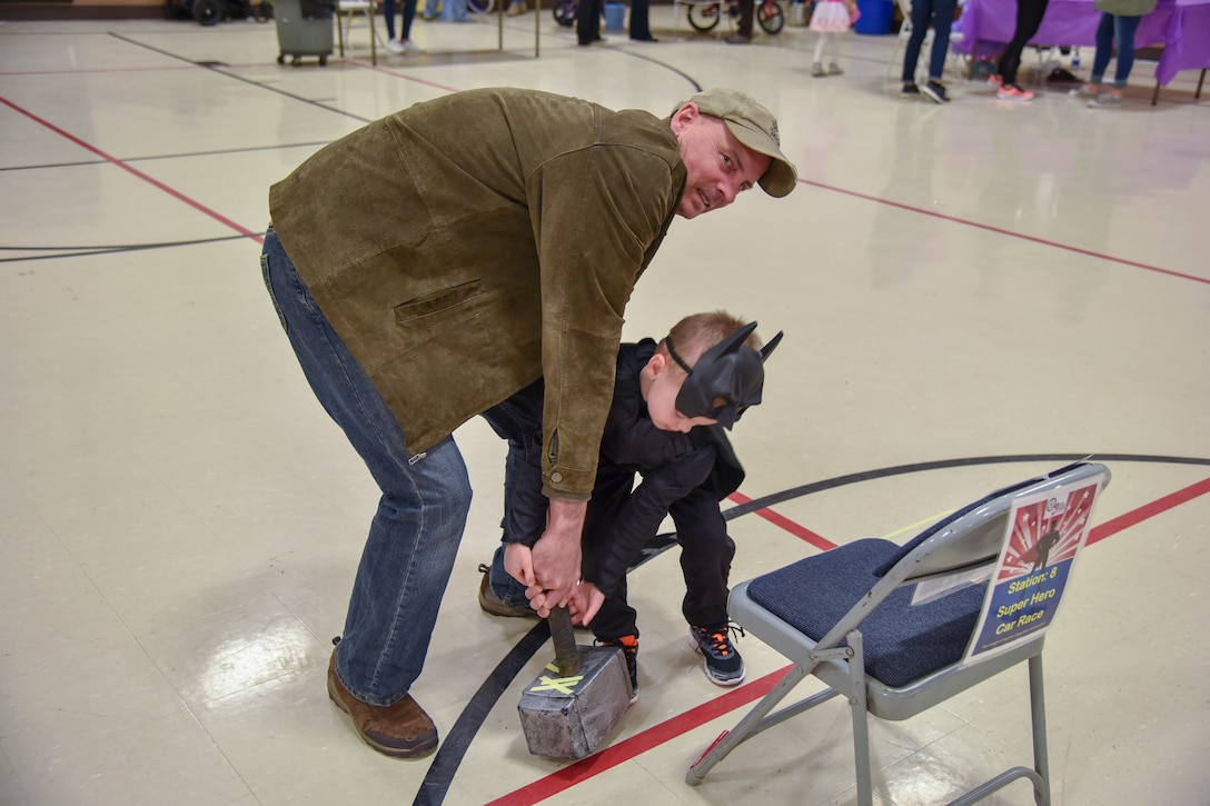 Senior Master Sgt. Dave Adams, 114th Communication Squadron communication plans and resources, and his son attempts to pull Thor's hammer during the Princess and Super Hero Day Camp April 7, 2018, at the National Guard Armory, Sioux Falls, S.D.