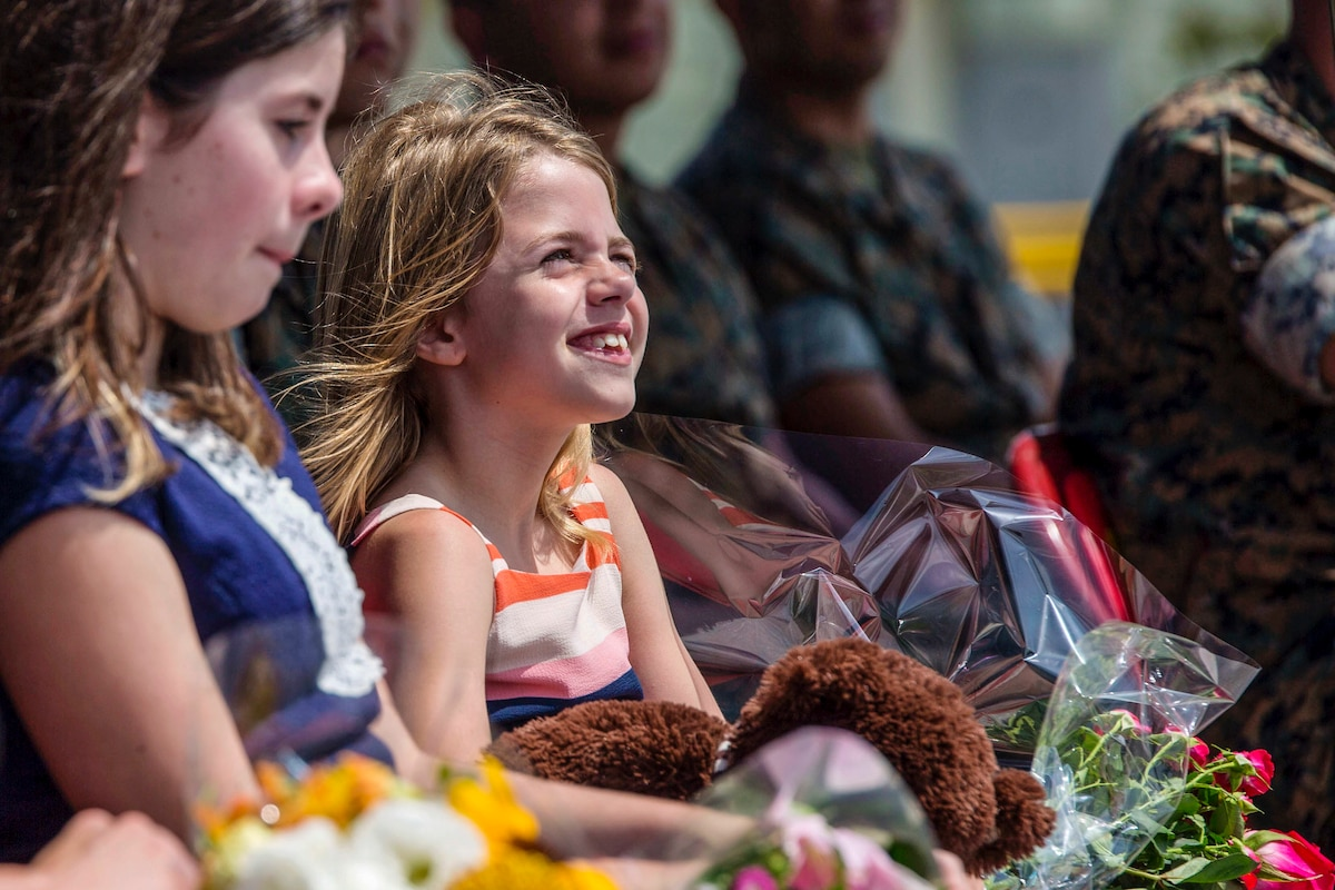 A smiling girl holds a stuffed animal and a bouquet as she sits in an audience of Marines.