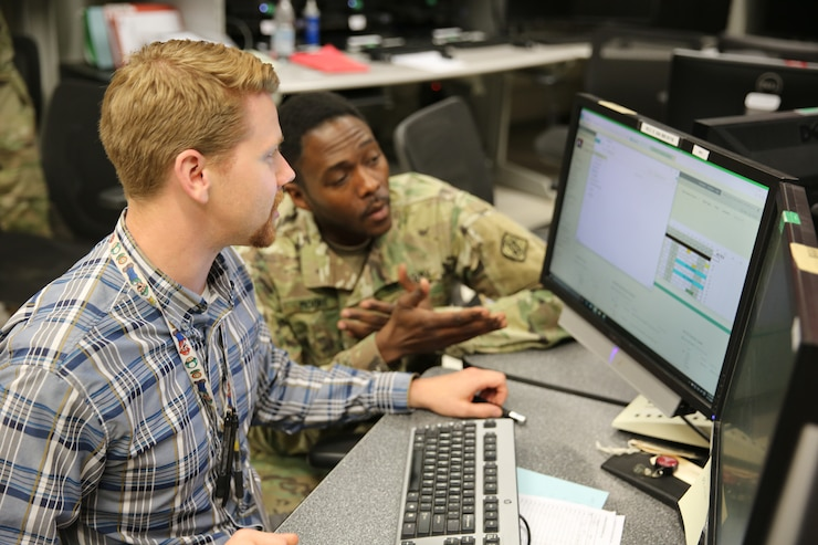 Soldier and civilian at computer