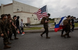 A Marine with 1st Marine Aircraft Wing carries the American Flag during the Bataan Death March Memorial hike, April 7, 2018 on Kadena Air Force base, Okinawa, Japan.  More than 200 service members and their families participated in the 8.5 mile hike around Kadena's perimeter in remembrance of the prisoners of war who perished as a result of the Death March that took place in the Philippine archipelago in 1942 during WWII.