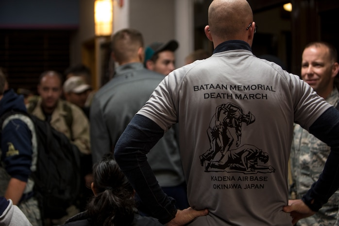 A volunteer gives out commemorative shirts to participants before the Bataan Death March Memorial hike, April 7, 2018 on Kadena Air Force base, Okinawa, Japan. More than 200 service members and their families participated in the 8.5 mile hike around Kadena's perimeter in remembrance of the prisoners of war who perished as a result of the Death March that took place in the Philippine archipelago in 1942 during WWII.
