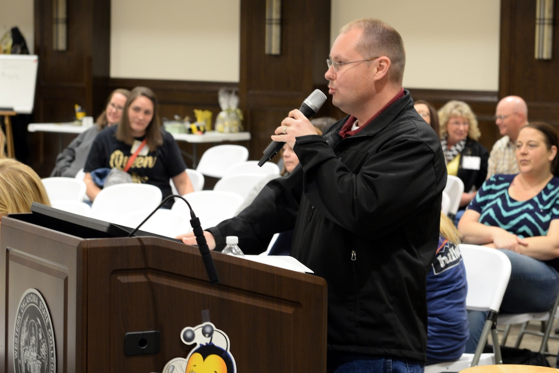 "U.S. Air Force Lt. Col. Jeremy Braswell, 97th Medical Support Squadron commander, pronounces words during the ""Grate"" Altus Spelling Bee, April 7, 2018, at Western Oklahoma State College, Altus, Okla."