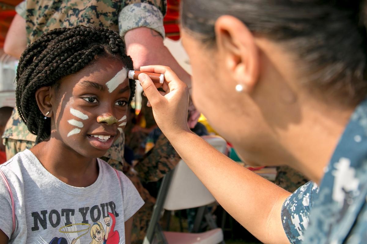 A sailor paints a child's face with paint.