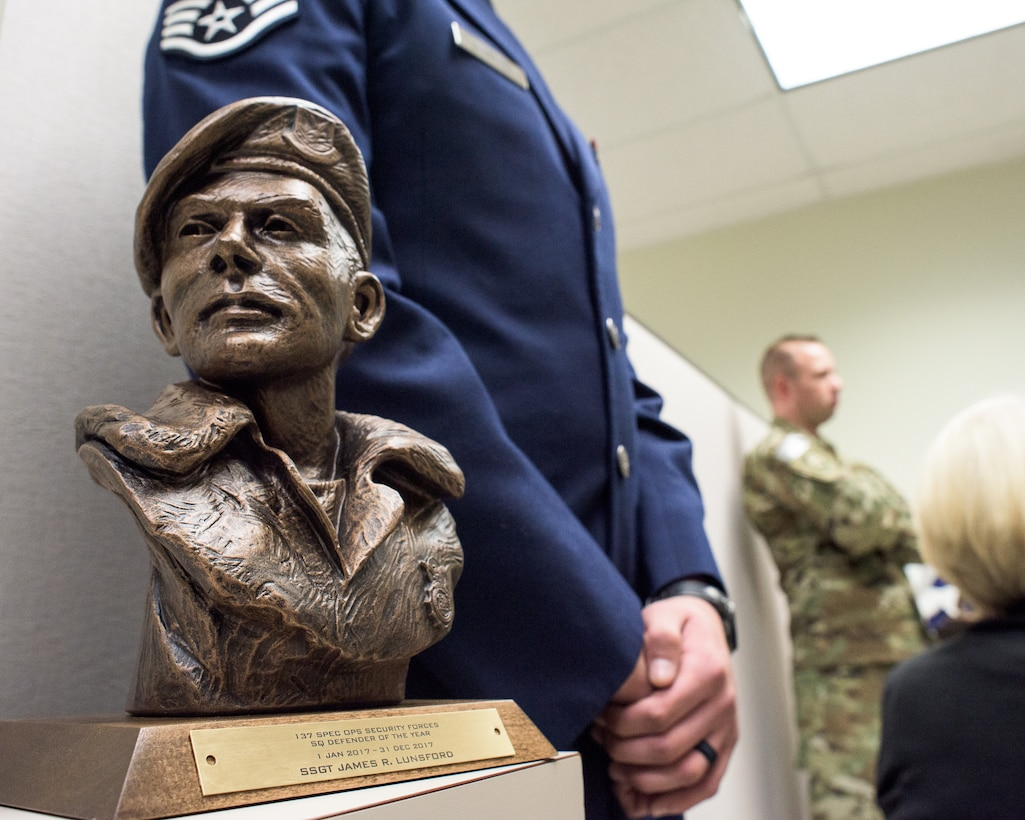 U.S. Air Force Staff Sgt. James Lunsford, 137th Special Operations Security Forces Squadron, stands beside the La Don Johnson award after receiving the honor at Will Rogers Air National Guard Base, Feb. 3, 2018. The La Don Johnson award is given by fellow security forces airmen for continued excellence during everyday duties. (U.S. Air National Guard photo by Tech. Sgt. Caroline Essex)