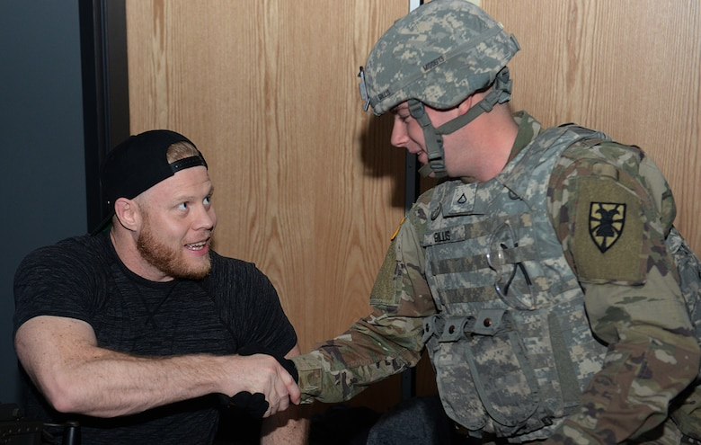 Eric Nicksick, Mixed Martial Arts coach and trainer, shakes hands with a U.S. Army Soldier during a tour at Joint Base Langley-Eustis, Va., April 5, 2018.