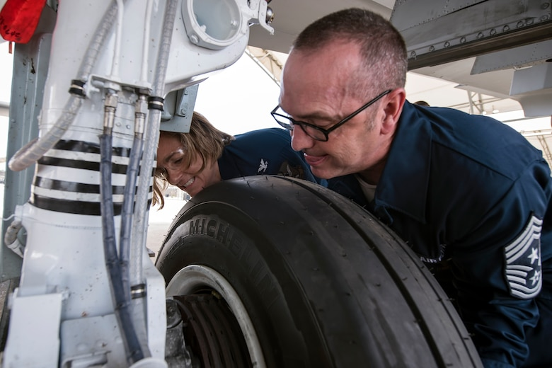 Chief Master Sgt. Jarrod Sebastian, right, 23d Wing command chief, and Col. Jennifer Short, left, 23d WG commander, push a tire into place, April 9, 2018, at Moody Air Force Base, Ga. Moody's leadership toured the 23d Aircraft Maintenance Squadron to get a better understanding of their overall mission, capabilities, and comprehensive duties. (U.S. Air Force photo by Airman Eugene Oliver)