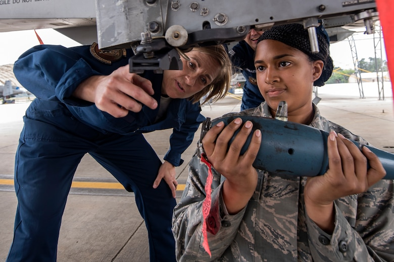 Col. Jennifer Short, left, 23d Wing commander, and Airman 1st Class Kenyah Smith, 74th Aircraft Maintenance unit weapons load crew member, install a training munition onto an A-10C Thunderbolt II during an immersion tour, April 9, 2018, at Moody Air Force Base, Ga. Moody's leadership toured the 23d Aircraft Maintenance Squadron to get a better understanding of their overall mission, capabilities, and comprehensive duties. (U.S. Air Force photo by Airman Eugene Oliver)