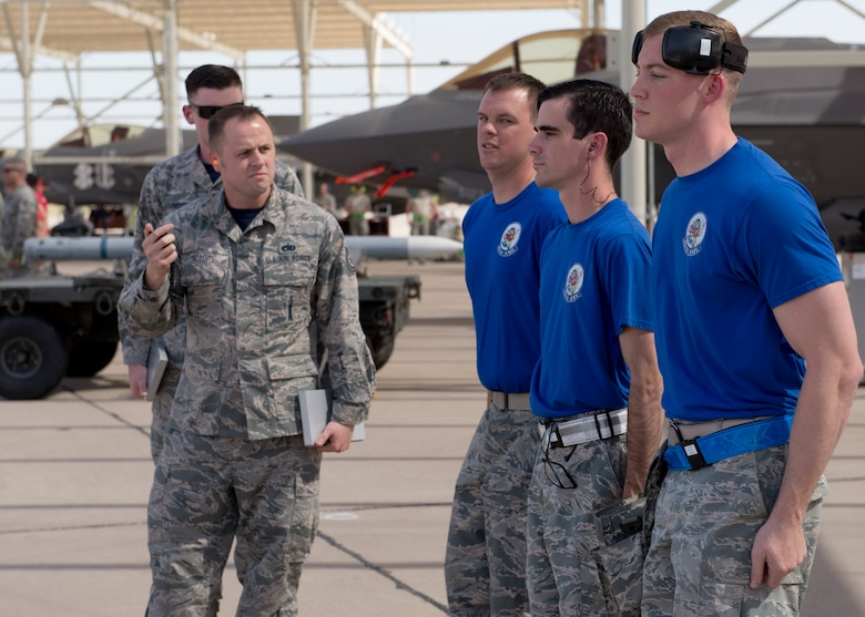 Judges start the timer on a weapons load crew from the 62nd Aircraft Maintenance Unit as they compete in the 2018 1st Quarter Load Crew Competition at Luke Air Force Base, Ariz., April 6. The team competed against others to load weapons onto a fighter aircraft correctly and safely in the fastest time. (U.S. Air Force photo by Senior Airman Ridge Shan)