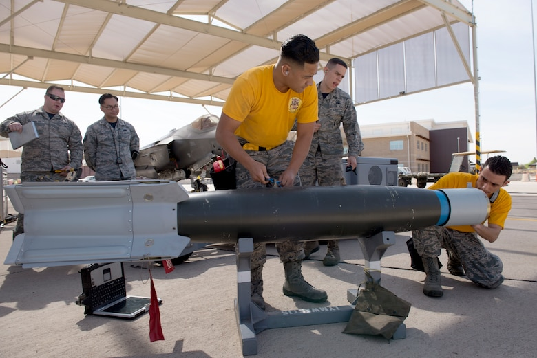 Airman 1st Class Ryan Tauoa, 61st Aircraft Maintenance Unit weapons load crew member, and Staff Sgt. Luis Santiago, 61st AMU weapons load crew lead, prepare an inert bomb for loading as judges observe during the 2018 1st Quarter Load Crew Competition at Luke Air Force Base, Ariz., April 6. Six teams from different AMUs competed to load F-16 Fighting Falcons and F-35 Lightning IIs. (U.S. Air Force photo by Senior Airman Ridge Shan)