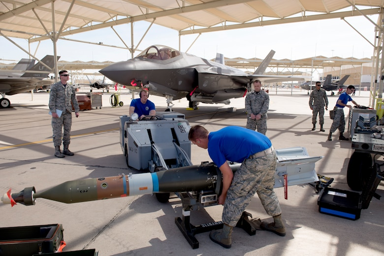 Judges observe as a weapons load crew from the 62nd Aircraft Maintenance Unit prepares an inert bomb for loading during the 2018 1st Quarter Load Crew Competition at Luke Air Force Base, Ariz., April 6. The 62nd AMU team beat five other teams to win the competition. (U.S. Air Force photo by Senior Airman Ridge Shan)