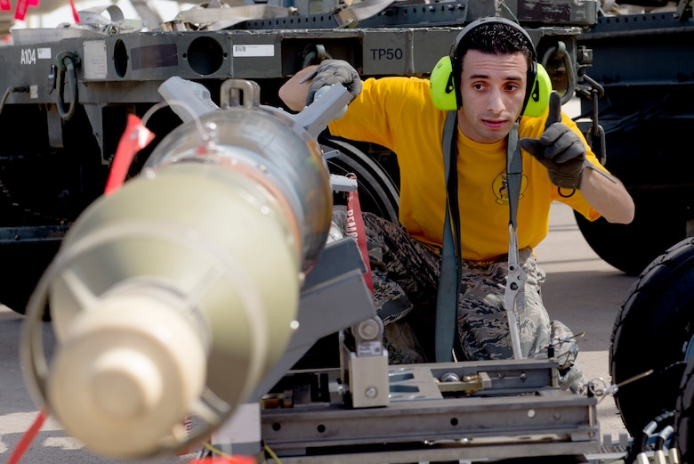 Staff Sgt. Luis Santiago, 61st Aircraft Maintenance Unit weapons load crew lead, prepares an inert bomb for loading during the 2018 1st Quarter Load Crew Competition at Luke Air Force Base, Ariz., April 6. The competition saw load crew teams from the 61st, 62nd, 63rd, 309th, 310th, and 425th AMUs compete to load a mock mission set of ordnance onto F-35 Lightning IIs and F-16 Fighting Falcons in the fastest time. (U.S. Air Force photo by Senior Airman Ridge Shan)
