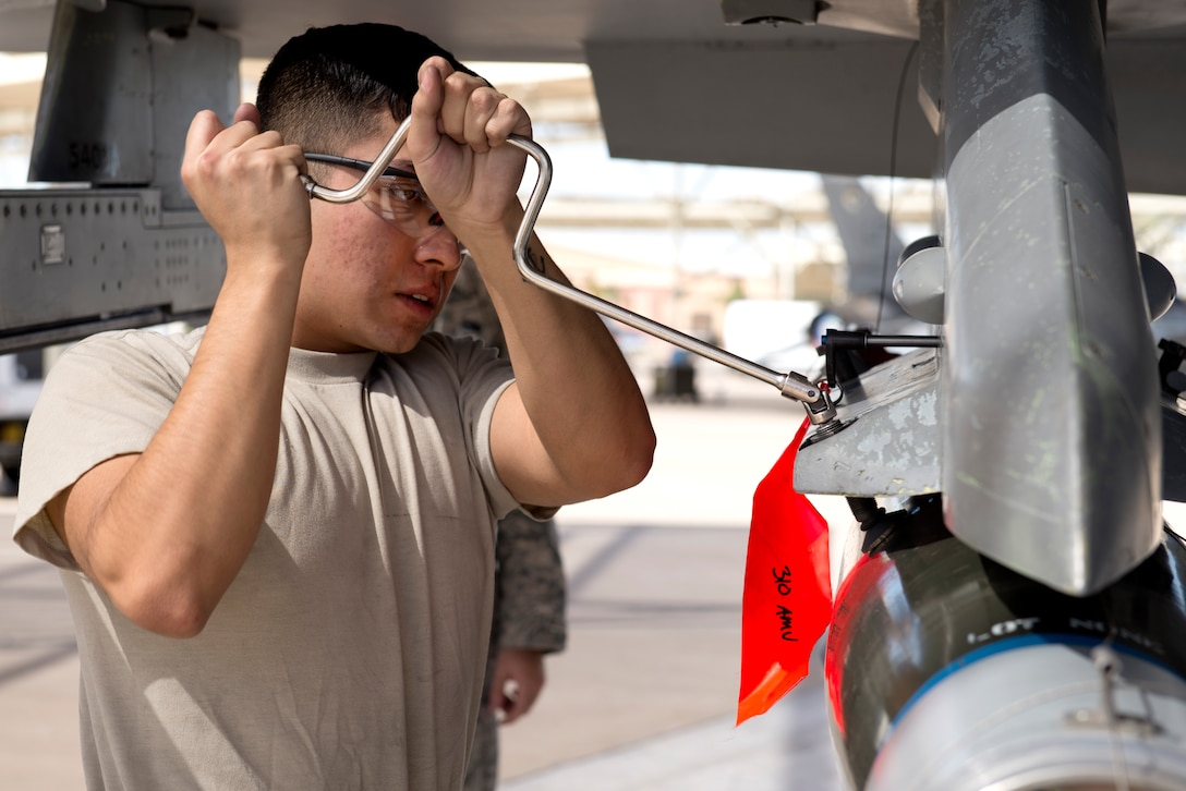 Airman Michael Gutierrez, 310th Aircraft Maintenance Unit weapons load crew member, attaches an inert bomb to an F-16 Fighting Falcon during the 2018 1st Quarter Load Crew Competition at Luke Air Force Base, Ariz., April 6. Teams of three load crew members used teamwork, communication, and technical knowledge to race to load weapons onto fighter aircraft under the watchful eye of experienced judges. (U.S. Air Force photo by Senior Airman Ridge Shan)