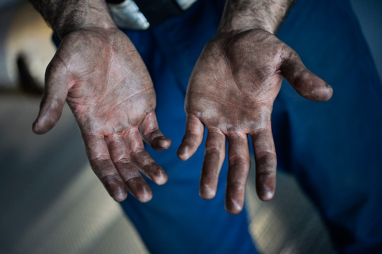 U.S. Air Force Senior Airman Johann Caballero, 86th Maintenance Squadron aerospace propulsion journeyman, shows oil on his hands as the result of conducting maintenance on the engine of a C-130J Super Hercules on Ramstein Air Base, Germany, April 10, 2018. Air Force maintainers are considered mission essential, and are responsible for ensuring the reliability and operational readiness of aircraft. (U.S. Air Force photo by Senior Airman Joshua Magbanua)