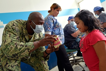 A military doctor hows a Guatemalan girl model teeth.