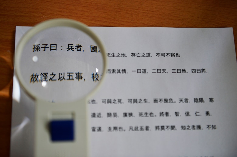 """A magnifying glass hovers over text from Sun Tzu's """"Art of War,"""" on Ramstein Air Base, Germany, April 3, 2017. The Air Force Culture and Language Center seeks to form a corps of multilingual Airmen to take on missions around the world through its Language Enabled Airman Program. (U.S. Air Force photo by Senior Airman Joshua Magbanua)"""