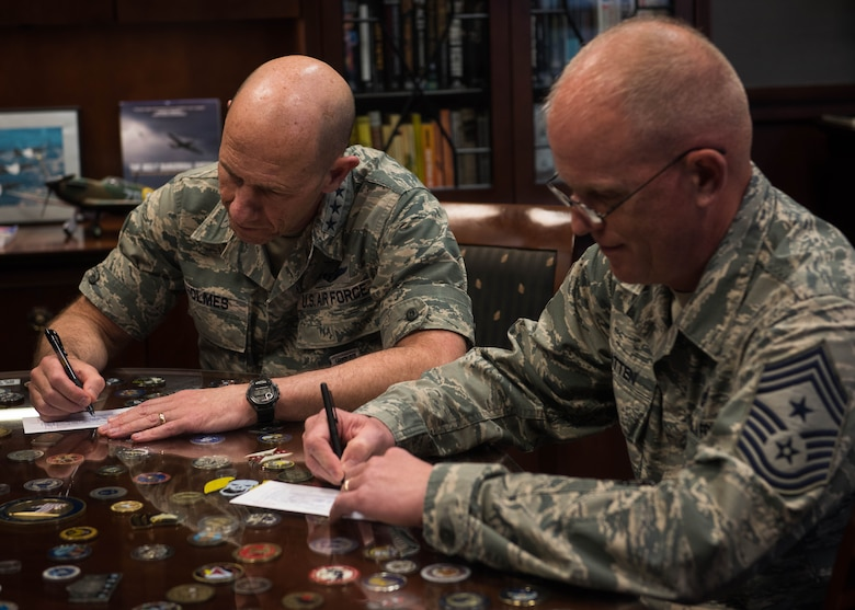 Gen. Mike Holmes, and Chief Master Sgt. Frank A. Batten II, of Air Combat Command, sign up for the 2018 Air Force Assistance Fund