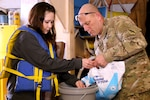 Soldier pours salt into a bucket while mentoring at a boat-builders youth program