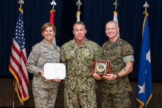 Chief Petty Officer Benjamin Allen, a senior non-commissioned officer at Joint Task Force Civil Support (JTF-CS), receives the Senior Non-Commissioned Officer (NCO) of the Year award from Air Force Gen. Lori Robinson and Marine Sgt. Maj. Paul McKenna at Peterson Air Force Base, Colo. Apr 4, 2018. To win this award, Allen competed against Senior NCOs from eight other units that fall under U.S, Northern Command. (Official DoD photo by Tech. Sgt. Joe Laws/released)