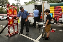 A firefighter demonstrates fire safety to a local child during Kids Fest in downtown Beaufort, April 7. April is Month of the Military Child and Child Abuse Prevention Month. The firefighter is with Beaufort County Fire and Rescue.