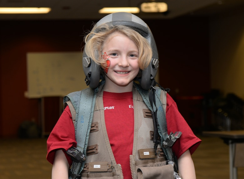 A child wears flight equipment during a kids deployment line at Ellsworth Air Force Base, S.D., April 7, 2018. The Month of the Military Child is celebrated in April to bring awareness to the important role the children of service members play in the armed forces community. (U.S. Air Force photo by Airman 1st Class Nicolas Z. Erwin)
