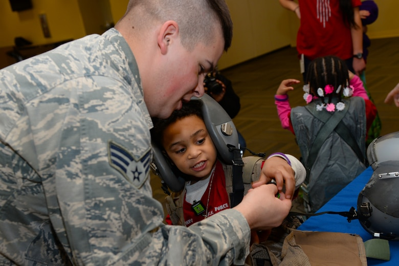 Senior Airman Cole Barnhart, a 28th Operations Support Squadron aircrew flight equipment technician, shows a child a compass during a kids deployment line at Ellsworth Air Force Base, S.D., April 7, 2018. Planning for this event took over three months of coordination with numerous base agencies. (U.S. Air Force photo by Airman 1st Class Nicolas Z. Erwin)
