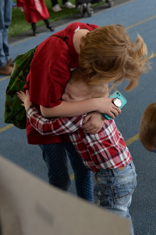 A child welcomes his sister back from a kids deployment line at Ellsworth Air Force Base, S.D., April 7, 2018. The groups of children were given 45 minutes to go through the deployment line, after which they were led back to the Pride Hangar where their families were waiting for them to return. (U.S. Air Force photo by Airman 1st Class Nicolas Z. Erwin)