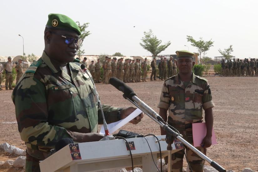 Military officer speaks at podium.