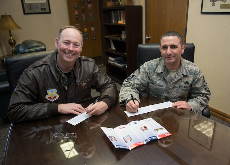 Col. David Berg, 55th Wing vice commander and Chief Master Sgt. Brian Kruzelnick, 55th Wing command chief, fill out a form in support of the Air Force Assistance Fund at the 55th Wing headquarters on Offutt Air Force Base, Neb., March 30, 2018.