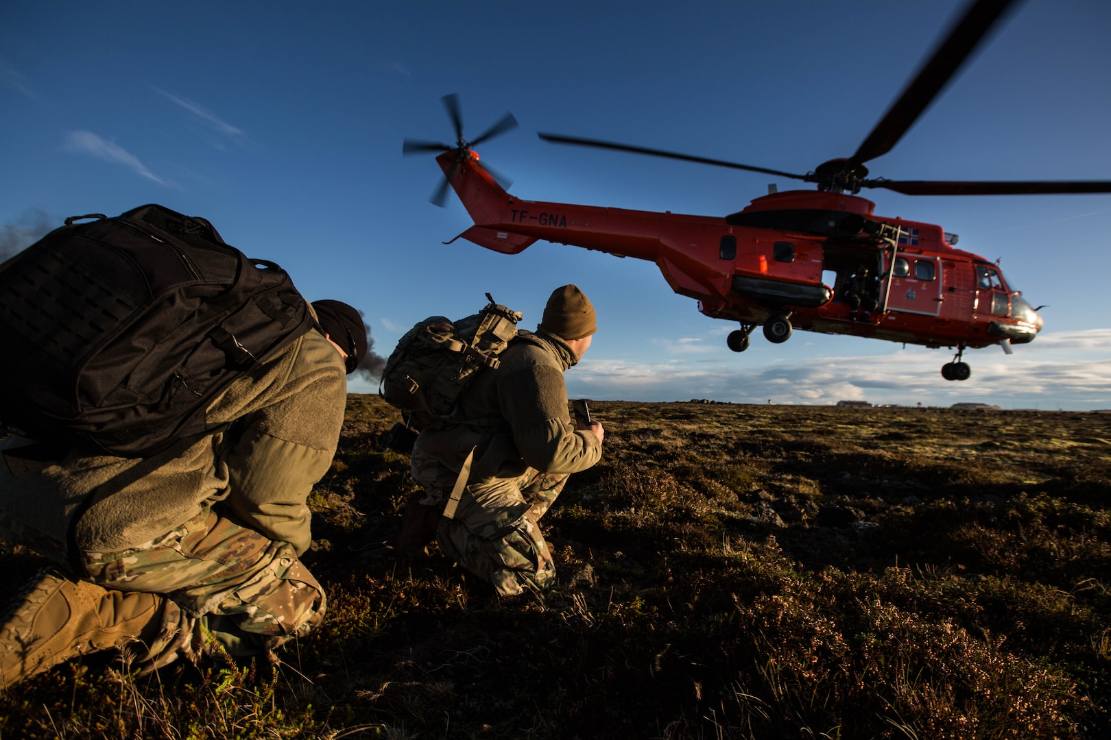 Army Explosive Ordnance Disposal Technicians look on as Icelandic coastguard helicopter takes off from field in Iceland during exercise Northern Challenge 2017 (NATO/Laurence Cameron)