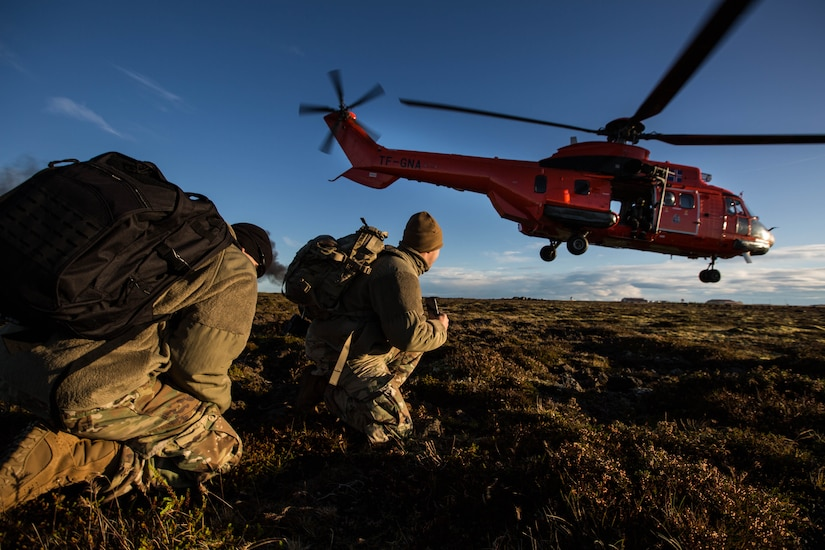 Army Explosive Ordnance Disposal Technicians look on as Icelandic coastguard helicopter takes off from field in Iceland during exercise Northern