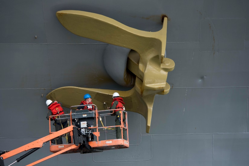 Servicemembers aboard USS Dwight D. Eisenhower paint starboard anchor gold, commemorating ship earning Retention Excellence Award for 2016,