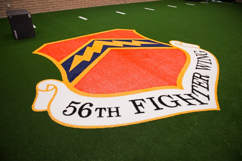 The 56th Fighter Wing insignia adorns the turf in the Tactical Integrated Training and Nutrition Arena April 9, 2018, at Luke Air Force Base, Ariz. The TITAN Arena will allow the professionals of the Human Performance Team to treat and develop fitness plans for pilots and other high-activity Airmen. (U.S. Air Force photo by Senior Airman Ridge Shan)