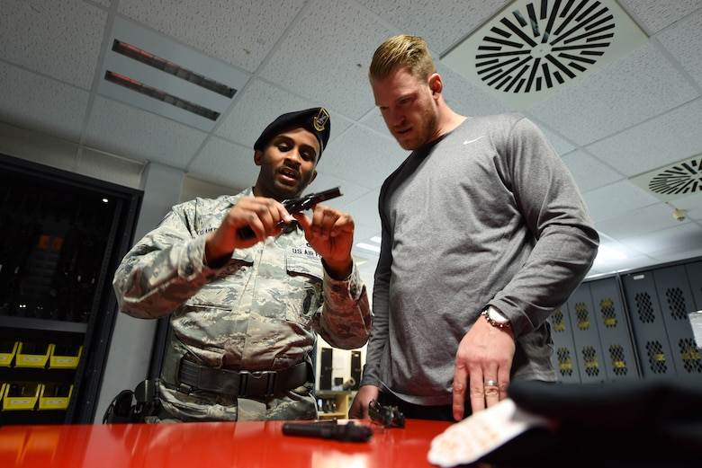 U.S. Air Force Tech. Sgt. Deandre Harrington, 86th Security Forces Squadron police services noncommissioned officer in charge, shows Kyle Rudolph, NFL Minnesota Vikings tight end, how to properly disassemble and clean an M9 handgun on Ramstein Air Base, Germany, April 6, 2018. Harrington explained to Rudolph that if proper care isn't taken with a firearm, it may misfire when needed.