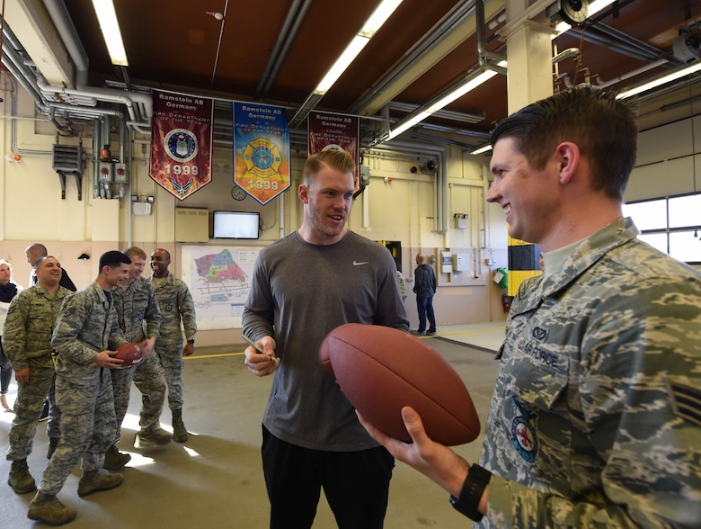 Firefighters from the 86th Civil Engineer Squadron receive autographs from Kyle Rudolph, NFL Minnesota Vikings tight end, after giving him a tour of the firehouse on Ramstein Air Base, Germany, April 6, 2018. The firefighters showed Rudolph how to put on the fire-retardant suit and demonstrated how to use some of the gear they use.