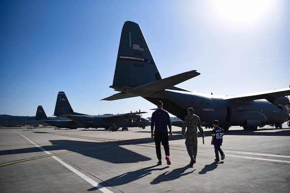 U.S. Air Force Tech. Sgt. Seth Wilkinson, 86th Aircraft Maintenance Squadron unit deployment manager, and his son walk with Kyle Rudolph, NFL Minnesota Vikings tight end, to a C-130J during Rudolph's visit to Ramstein Air Base, Germany, April 7, 2018. Rudolph spent four days in the Kaiserslautern Military Community. During this time, he toured Ramstein Air Base, Kapaun Air Base, Vogelweh and Sembach. He spoke with Airmen, took pictures with them and signed autographs. On April 7th and 8th, Rudolph hosted a football camp at the Kaiserslautern High School football stadium where he emphasized the fundamentals of the game.