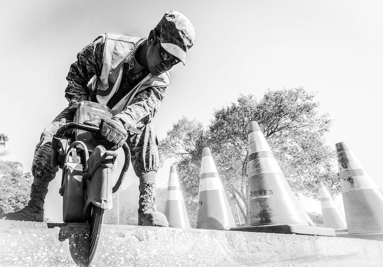 U.S. Air Force Staff Sgt. Jacob Robinson, 20th Civil Engineer Squadron pavement and construction journeyman, uses a K-12 saw to cut through asphalt at Shaw Air Force Base, S.C., April 12, 2018.